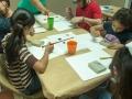 Participantes del taller pintando con gomitas elásticas amarradas a bloques de madera