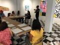 Artista residente explicandole a los participantes sobre el taller